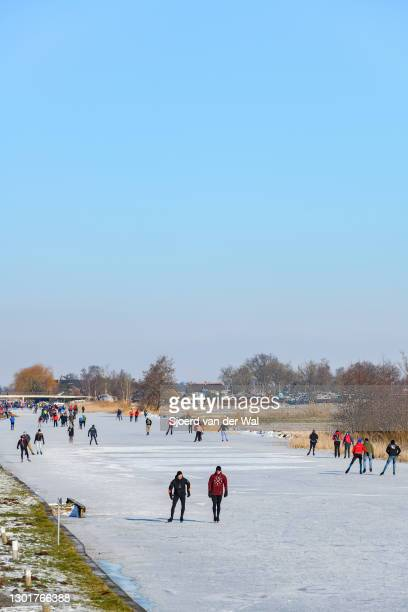 People ice skating on a frozen canal in the Weerribben-Wieden nature reserve in Overijssel during a cold winter day in The Netherlands on February...