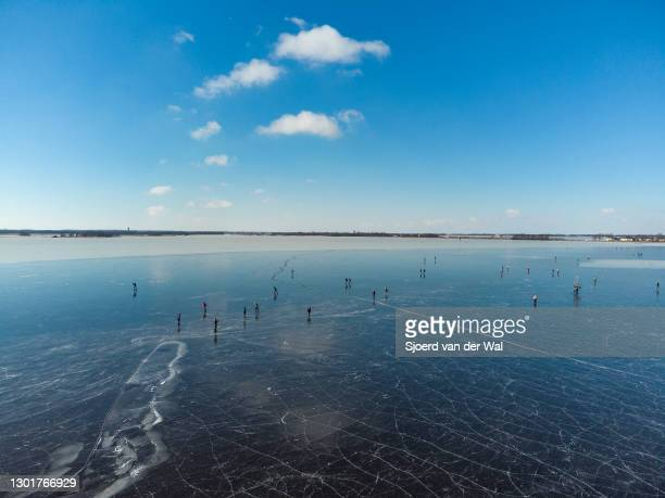 People ice skating on a frozen lake in the Weerribben-Wieden nature reserve in Overijssel during a cold winter day in The Netherlands on February 12,...