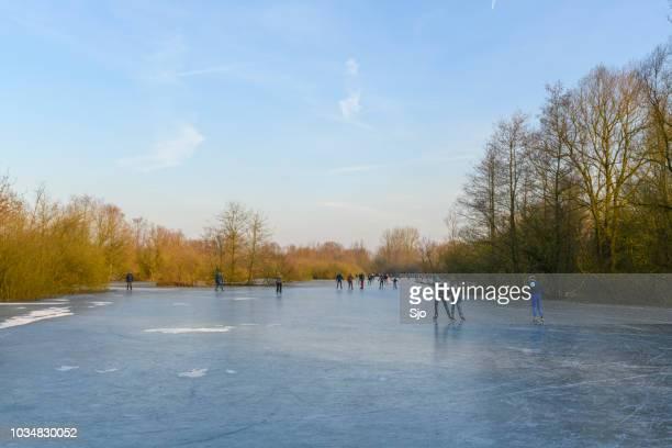 Mensen schaatsen op een bevroren meer naast de rivier de IJssel in de buurt van Zwolle
