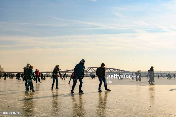People ice skating on a frozen lake next to the river IJssel near Zwolle