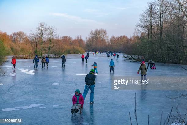 mensen schaatsen op een bevroren meer naast de ijssel bij zwolle - schaatsen stockfoto's en -beelden