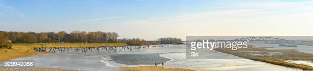 people ice skating on a frozen lake next to the river ijssel near zwolle - zwolle stock photos and pictures