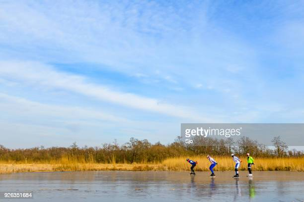 People ice skating on frozen canals in the Weerribben Wieden nature reserve in Holland