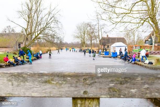 people ice skating on frozen canals in the weerribben wieden nature reserve in holland - overijssel stock pictures, royalty-free photos & images