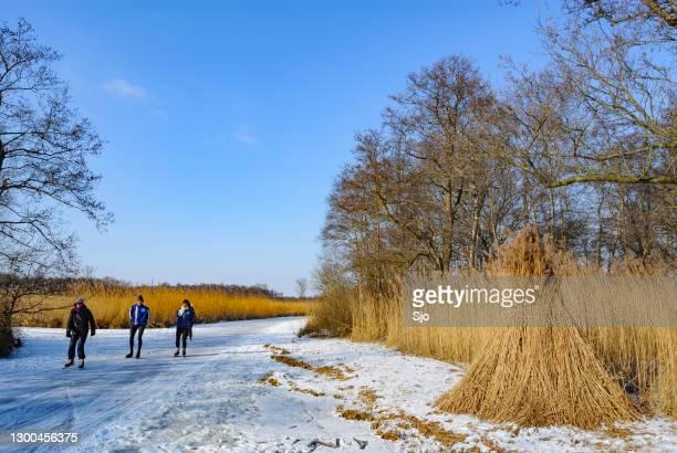 tijdens een mooie winterdag schaatsen op bevroren waterwegen in natuurgebied de weerribben wieden - schaats ijs stockfoto's en -beelden