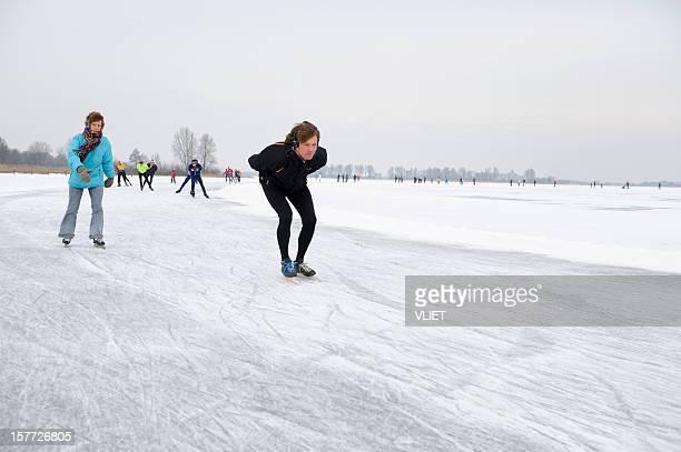 people ice-skating on a lake in the netherlands - schaats ijs stockfoto's en -beelden