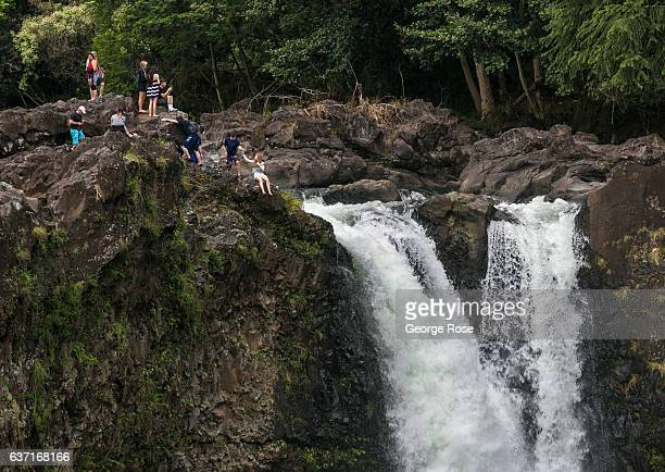 People ignoring posted signs risk their lives to take selfies along the rocky cliffs at Rainbow Falls on December 12 near Hilo, Hawaii. Hawaii, the...