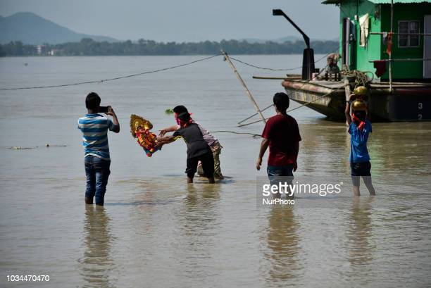 People immerse Viswakarma idol in the Brahmaputra river as Vishwakarma puja tomorrow and new idol to bought for puja in Guwahati Assam India on...
