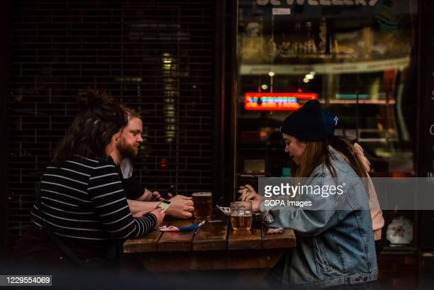 People in a bar enjoying an evening drink without masks on Chapel street, one of the most iconic streets of Melbourne.
