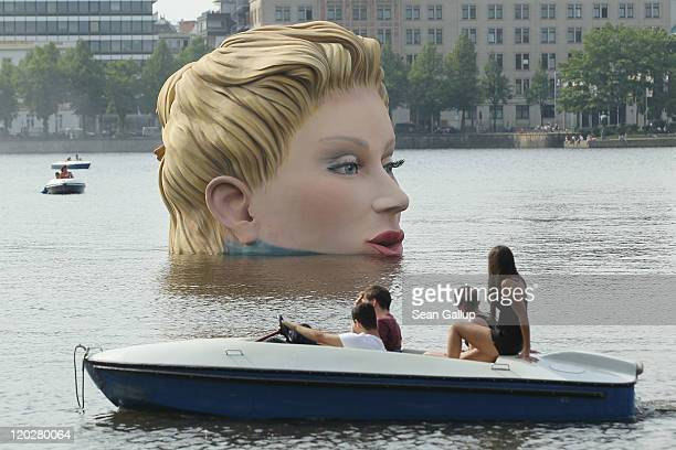 People in a boat approach Die Badende a giant sculpture showing a woman's head and knees as if she were resting in the Binnenalster lake on August 3...