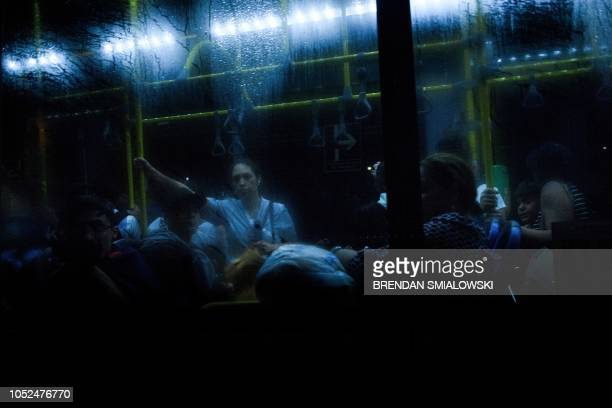 TOPSHOT People in a bus watch as a motorcade with US Secretary of State Mike Pompeo travels to Tocumen International Airport October 18 2018 in...