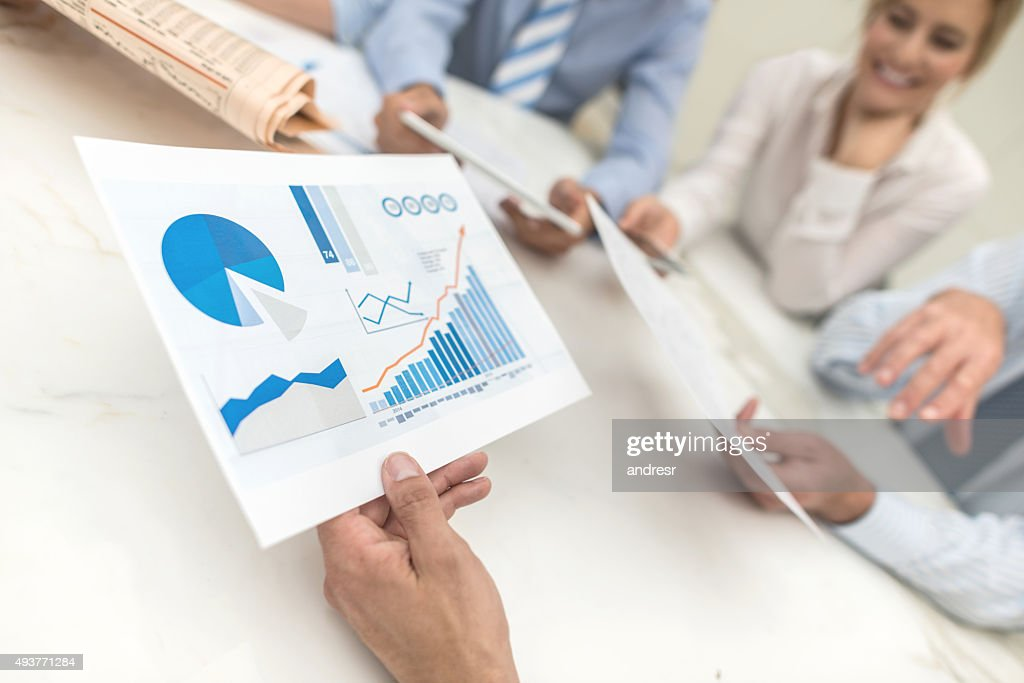 People in a business meeting checking the market behaviour : Stock Photo