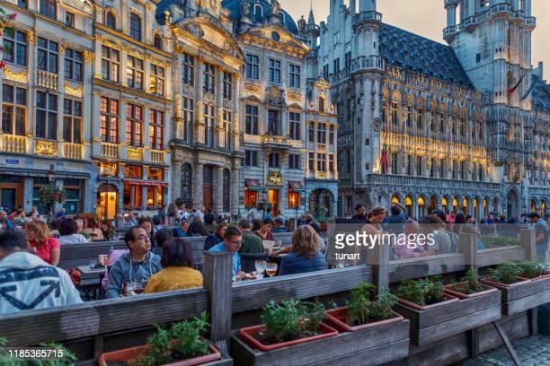 people in a cafe in grand place square in brussels, belgium - região de bruxelas capital imagens e fotografias de stock