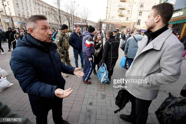 People in a crowd are seen arguing near an exhibit with cutout figures of presidential candidates including a figure of Russian president Vladimir...