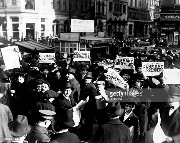 People in a crowd at Times Square hold up newspaper extras reporting the signing of the armistice. The government report that the news was not true...