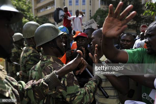 People in a crowd of supporters of Kenya's main opposition National Super Alliance presidential flagbearer Raila Odinga argue with police officers...