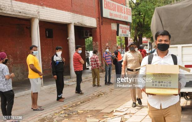 People in a long queue outside liquor shops in Sector 32 during lockdown, on May 4, 2020 in Chandigarh, India. A large number of people were seen...