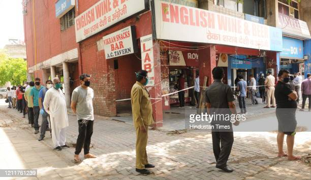 People in a long queue outside liquor shops in Sector 32 during lockdown on May 4 2020 in Chandigarh India A large number of people were seen queuing...