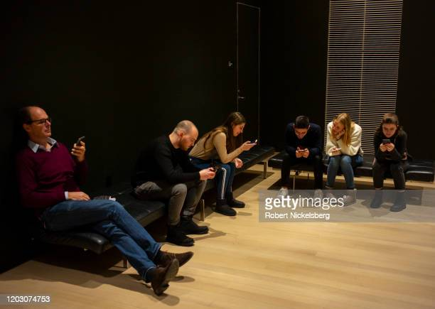 People in a lounge area at the Museum of Modern Art MOMA look at their iPhones in New York City January 27 2020 The museum is often identified as one...