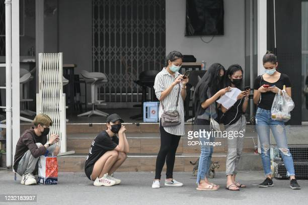 People in a queue for verification of their documents during a swab test drive outside a nightclub in Bangkok. The Ministry of Public Health is set...
