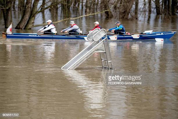 People in a rowing boat make their way past a slide surrounded by the floods of the river Rhine in Cologne western Germany on January 24 2018 / AFP...