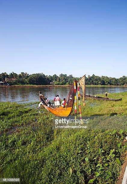 People in a snake boat at the riverside Aranmula Kerala India