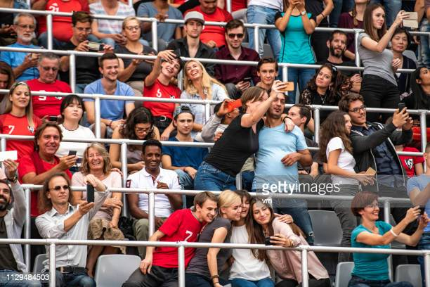 people in a stadium taking selfies - sports event stock pictures, royalty-free photos & images