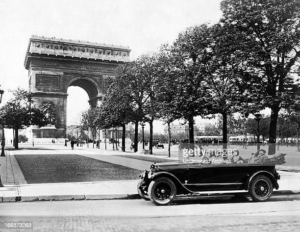 People in a touring car at the Arc de Triomphe de l'Etoile at the western end of the ChampsElysees Paris France circa 1929