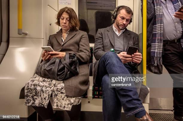 personas en un tren subterráneo en londres - vertical red tube fotografías e imágenes de stock