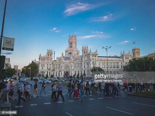 People in a zebra crossing and palacio de Comunicaciones illuminated at twilight in Madrid Spain