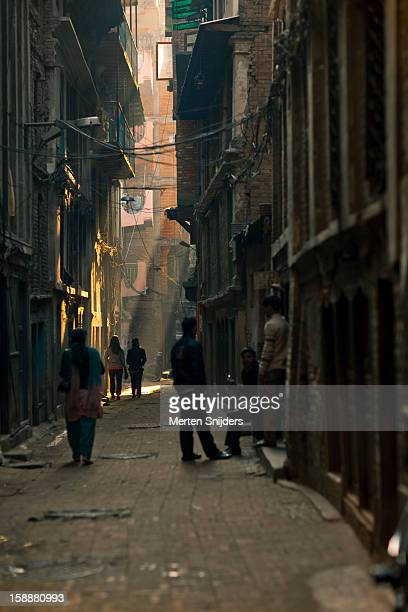 people in an alley during morning - merten snijders stockfoto's en -beelden