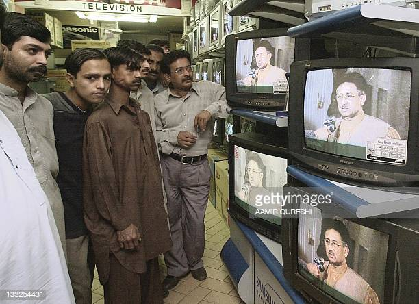 People in an electronic market watch Pakistan's President Pervez Musharraf's giving an interview on a state run television over the murder of US...