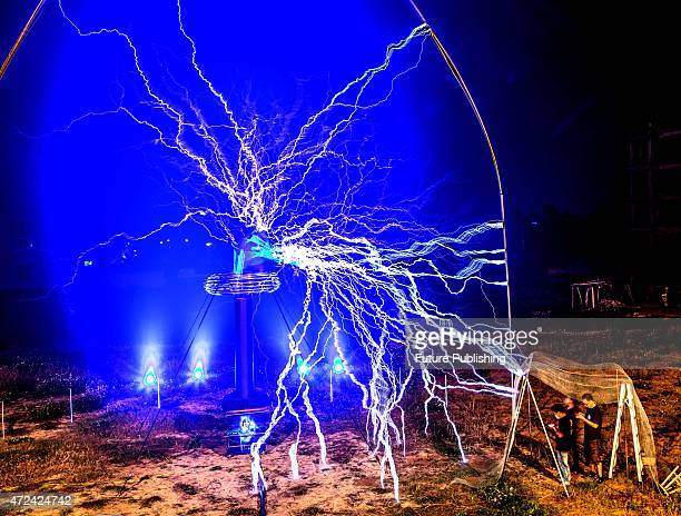 People in an iron mesh shelter watch a man in an iron mesh suit playing with manmade lightening during a show on April 29 2015 in Changle China...