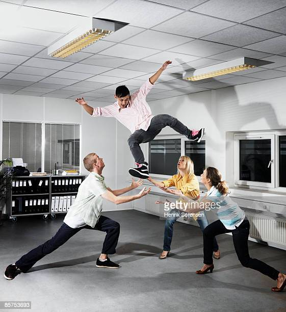 3 people in an office throwing a 4th person in the - homem pegando mulher imagens e fotografias de stock