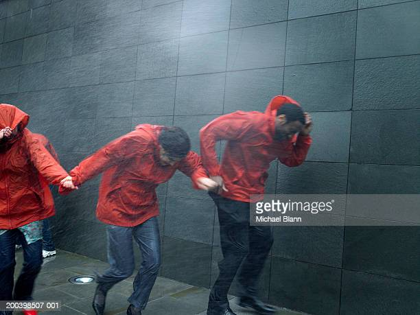 people in anoraks struggling to walk against rainstorm - gale stock photos and pictures