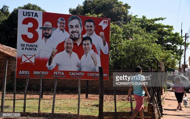 People in Asuncion on December 16 2017 walk by a billboard will electoral propaganda of Mario Abdo Benitez one of the ruling party's candidates for...