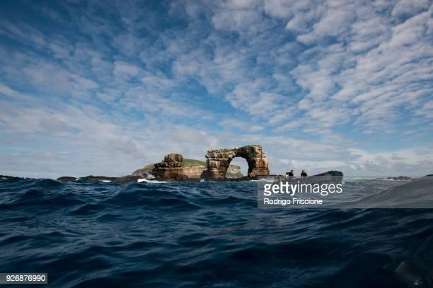 people in boat by darwins arch, darwin island, seymour, galapagos, ecuador, south america - darwin island stock photos and pictures