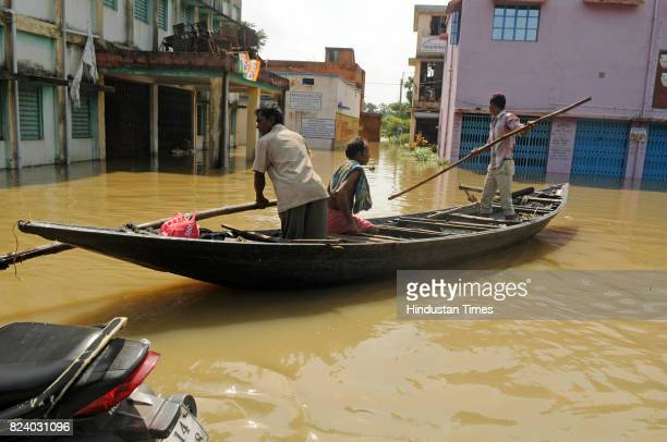 People in boat get to the safety in flood affected Shehagori village of Amta Block II Howrah on July 28 2017 near Kolkata India Flood situation in...