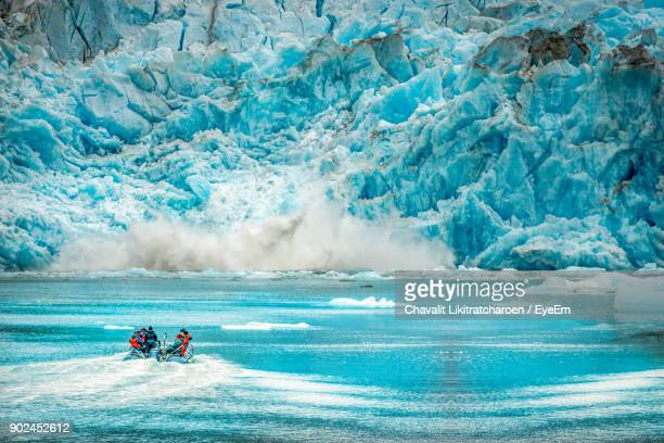 People In Boat On River Against Frozen Mountain