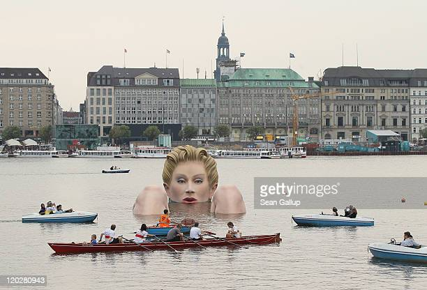 People in boats approach Die Badende a giant sculpture showing a woman's head and knees as if she were resting in the Binnenalster lake on August 3...