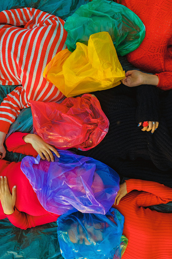 People in bright colored clothes with plastic bags on their heads - gettyimageskorea