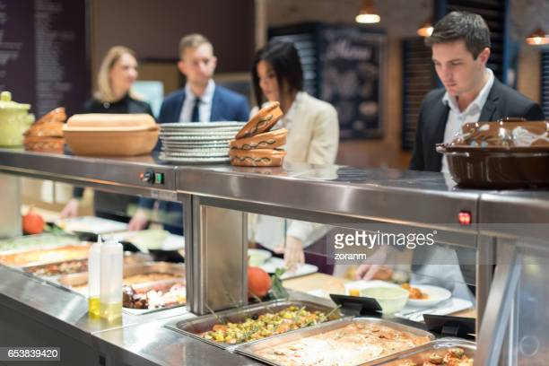 people in canteen waiting in line - food state stock pictures, royalty-free photos & images