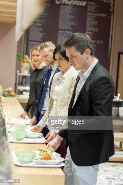 ラインで待っている食堂の人々 - セルフサービス ストックフォトと画像