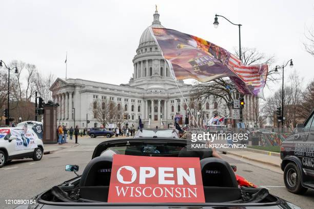 People in cars participate in a protest against the coronavirus shutdown in front of State Capitol in Madison Wisconsin on April 24 2020 Gyms hair...
