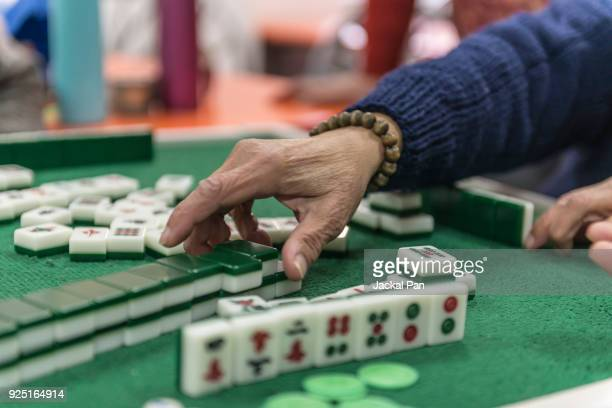 people in china playing chinese mahjong tiles - mahjong stock photos and pictures