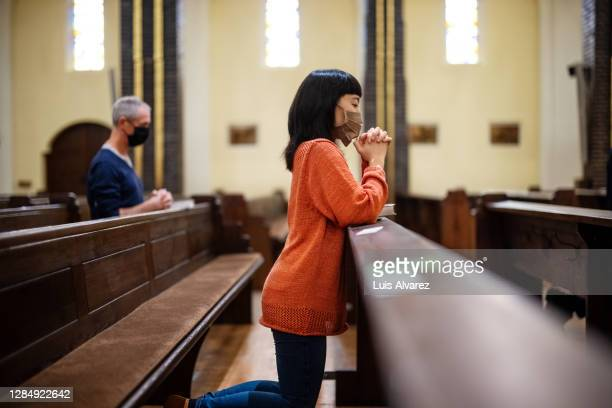 people in church praying with covid-19 restrictions - religion stock pictures, royalty-free photos & images
