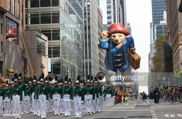 People in colorful costumes carry cartoon characters' balloons during 89th Annual Macys Thanksgiving Day Parade in New York USA on November 26 2015
