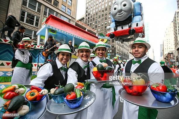 People in colorful costumes pose with plastic fruits and vegetables during 89th Annual Macys Thanksgiving Day Parade in New York USA on November 26...