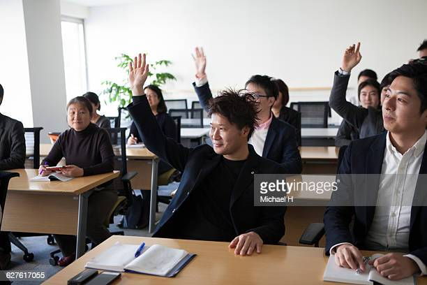 people in conference room with raising hand