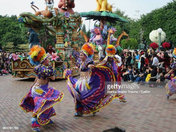 people in costume dancing on footpath during event - performing arts event photos et images de collection